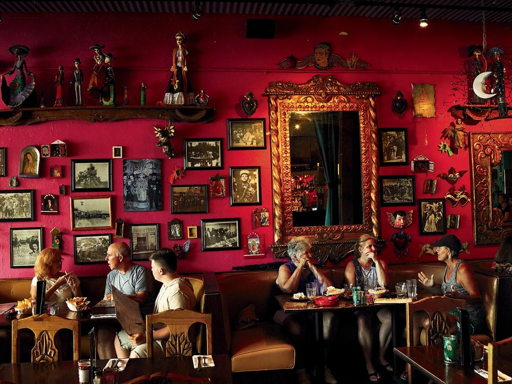 Six dinners eating at Casa Tina restaurant in Dunedin. The wall is red and decorated with multiple portraits.