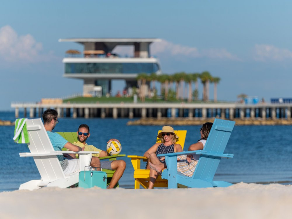 Four friend lounge in Adirondack chairs at spa beach at the new St. Pete Pier